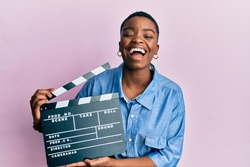 Young african american woman holding video film clapboard smiling and laughing hard out loud because funny crazy joke.