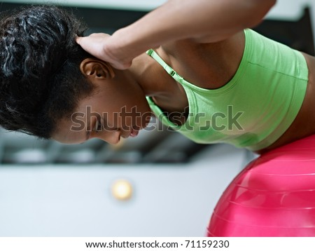 young african american woman in green sportswear exercising back muscles on fit ball in gym. Horizontal shape, side view, copy space