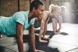 Young African American woman in sportswear smiling while doing pushups with a group of friends during a workout class at the gym