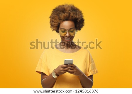 Young african american woman in yellow t-shirt and trendy eyeglasses looking at screen of phone and smiling nicely while chatting  #1245816376