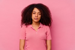 Young african american woman isolated on pink background sad, serious face, feeling miserable and displeased.
