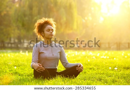 Young african american woman meditating in nature