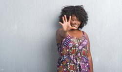 Young african american woman over grey grunge wall wearing colorful dress showing and pointing up with fingers number five while smiling confident and happy.