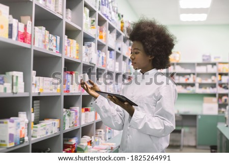 Young African American woman pharmacist or chemist using digital tablet, while standing near the shelves with medicines in modern pharmacy during drugs inventory