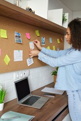 Young african american woman pin weekly planning sticker on mood board at home office. Black girl put post it sticky note memo on board to organize work goals, self organization concept. Vertical