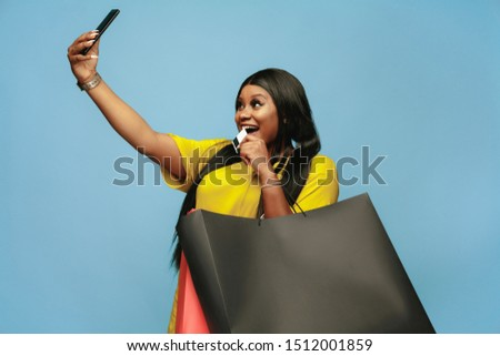 Young african-american woman shopping with colorful packs on blue background. Attractive female model. Finance, black friday, sales, concept. Copyspace. Making selfie or vlog with payment card.