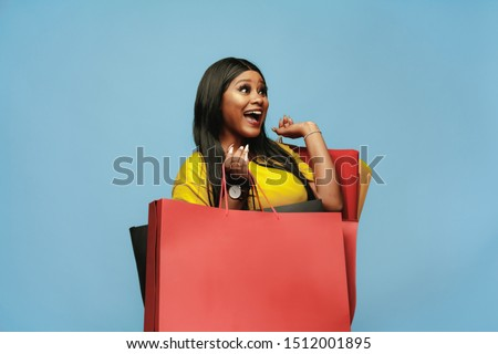 Young african-american woman shopping with colorful packs on blue background. Attractive female model. Finance, black friday, cyber monday, sales, autumn concept. Copyspace. Smiling, looks happy.