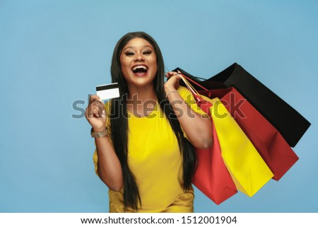 Young african-american woman shopping with colorful packs on blue background. Attractive female model. Finance, black friday, cyber monday, sales, autumn concept. Copyspace. Using payment card.