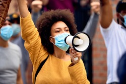 Young African American woman shouting through megaphones while supporting anti-racism protests.