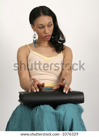Young African American woman sitting impatiently with portfolio in her lap