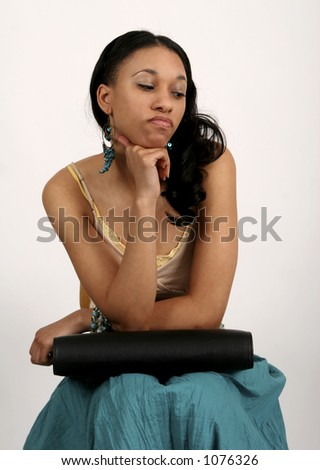 Young African American woman sitting with portfolio in her lap, looking bored