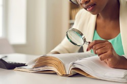 Young african american woman skeptically looking via magnifying glass at paper document. Female auditor analyzing bills, searching tax information. Finance analysis, bookkeeping, research work