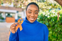 Young african american woman smiling happy holding orange awareness ribbon at the park.
