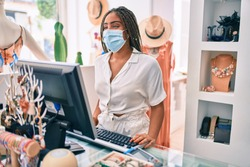 Young african american woman smiling happy working at the till wearing coronavirus safety mask at retail shop