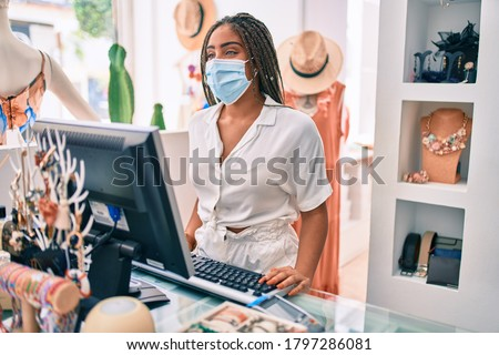 Young african american woman smiling happy working at the till wearing coronavirus safety mask at retail shop Сток-фото ©