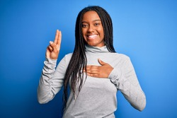 Young african american woman standing wearing casual turtleneck over blue isolated background smiling swearing with hand on chest and fingers up, making a loyalty promise oath