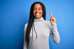 Young african american woman standing wearing casual turtleneck over blue isolated background showing and pointing up with finger number one while smiling confident and happy.