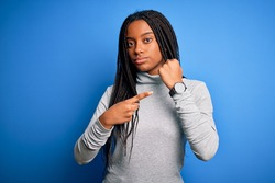 Young african american woman standing wearing casual turtleneck over blue isolated background In hurry pointing to watch time, impatience, looking at the camera with relaxed expression