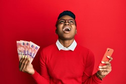 Young african american woman using smartphone holding south africa rand banknotes angry and mad screaming frustrated and furious, shouting with anger looking up.