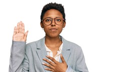 Young african american woman wearing business clothes swearing with hand on chest and open palm, making a loyalty promise oath