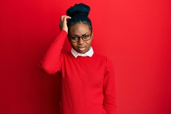 Young african american woman wearing casual clothes and glasses confuse and wonder about question. uncertain with doubt, thinking with hand on head. pensive concept.
