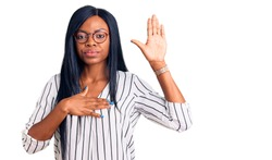 Young african american woman wearing casual clothes and glasses swearing with hand on chest and open palm, making a loyalty promise oath