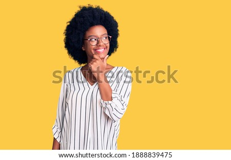 Young african american woman wearing casual clothes and glasses with hand on chin thinking about question, pensive expression. smiling with thoughtful face. doubt concept.
