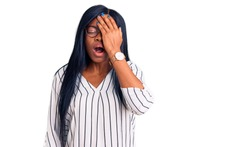 Young african american woman wearing casual clothes and glasses yawning tired covering half face, eye and mouth with hand. face hurts in pain.