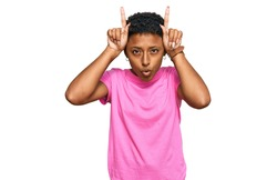 Young african american woman wearing casual clothes doing funny gesture with finger over head as bull horns