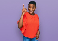 Young african american woman wearing casual clothes pointing finger up with successful idea. exited and happy. number one.