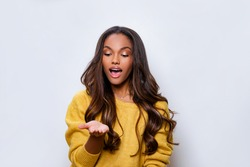 Young african american woman wearing casual clothes smiling with hand palm receiving or giving gesture hold and protection. Black Girl model looks at hand with admiration, mouth open.