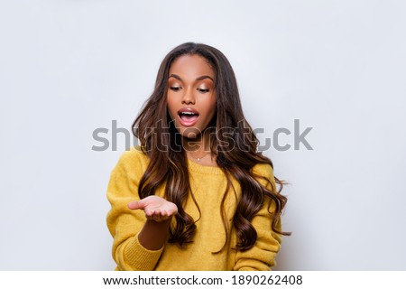 Young african american woman wearing casual clothes smiling with hand palm receiving or giving gesture hold and protection. Black Girl model looks at hand with admiration, mouth open.              Stock photo ©