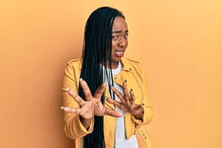 Young african american woman wearing casual jacket disgusted expression, displeased and fearful doing disgust face because aversion reaction. with hands raised