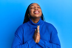 Young african american woman wearing casual winter sweater begging and praying with hands together with hope expression on face very emotional and worried. begging.