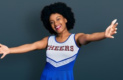 Young african american woman wearing cheerleader uniform looking at the camera smiling with open arms for hug. cheerful expression embracing happiness.