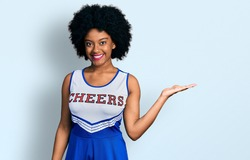 Young african american woman wearing cheerleader uniform smiling cheerful presenting and pointing with palm of hand looking at the camera.