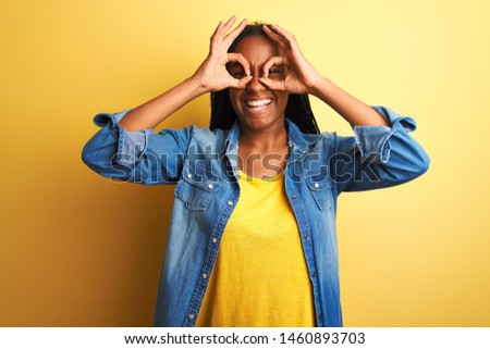 Young african american woman wearing denim shirt standing over isolated yellow background doing ok gesture like binoculars sticking tongue out, eyes looking through fingers. Crazy expression.