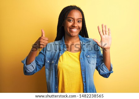 Young african american woman wearing denim shirt standing over isolated yellow background showing and pointing up with fingers number six while smiling confident and happy.
