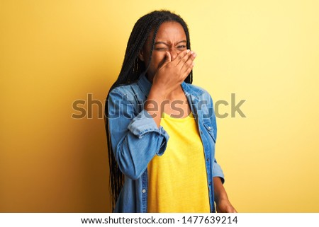 Young african american woman wearing denim shirt standing over isolated yellow background smelling something stinky and disgusting, intolerable smell, holding breath with fingers on nose. Bad smells