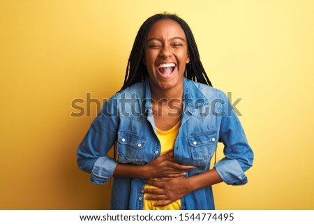 Young african american woman wearing denim shirt standing over isolated yellow background smiling and laughing hard out loud because funny crazy joke with hands on body.