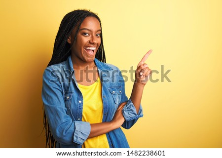 Young african american woman wearing denim shirt standing over isolated yellow background with a big smile on face, pointing with hand finger to the side looking at the camera.