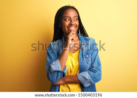 Young african american woman wearing denim shirt standing over isolated yellow background with hand on chin thinking about question, pensive expression. Smiling and thoughtful face. Doubt concept.