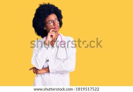 Young african american woman wearing doctor coat and stethoscope with hand on chin thinking about question, pensive expression. smiling with thoughtful face. doubt concept.