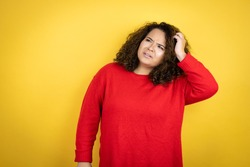 Young african american woman wearing red sweater over yellow background confuse and wonder about question. Uncertain with doubt, thinking with hand on head