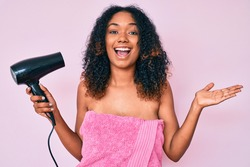 Young african american woman wearing shower towel holding dryer celebrating victory with happy smile and winner expression with raised hands
