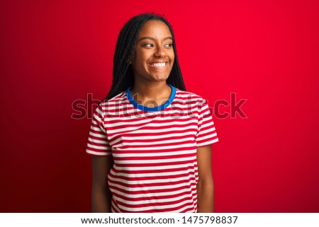 Young african american woman wearing striped t-shirt standing over isolated red background looking away to side with smile on face, natural expression. Laughing confident. #1475798837