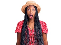 Young african american woman wearing summer hat afraid and shocked with surprise and amazed expression, fear and excited face.