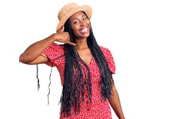 Young african american woman wearing summer hat smiling doing phone gesture with hand and fingers like talking on the telephone. communicating concepts.