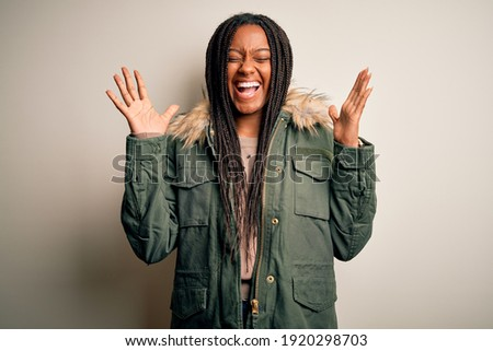 Young african american woman wearing winter parka coat over isolated background celebrating mad and crazy for success with arms raised and closed eyes screaming excited. Winner concept Сток-фото ©