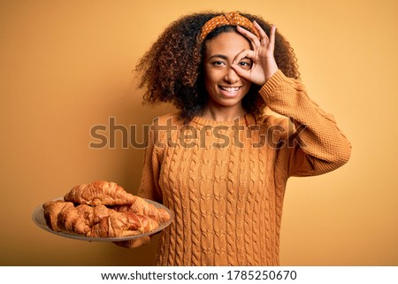 Young african american woman with afro hair holding croissants over yellow background with happy face smiling doing ok sign with hand on eye looking through fingers Stock fotó ©